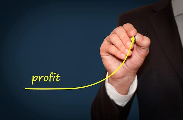 Biznesmen rysuje rosnącą linię symbolizującą rosnące zyski