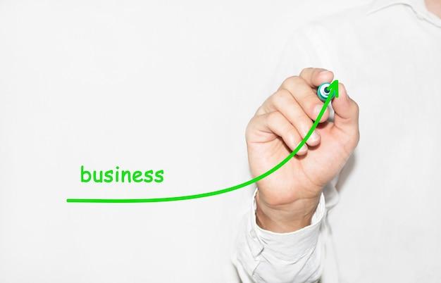 Biznesmen rysuje rosnący wykres symbolizujący rozwijający się biznes