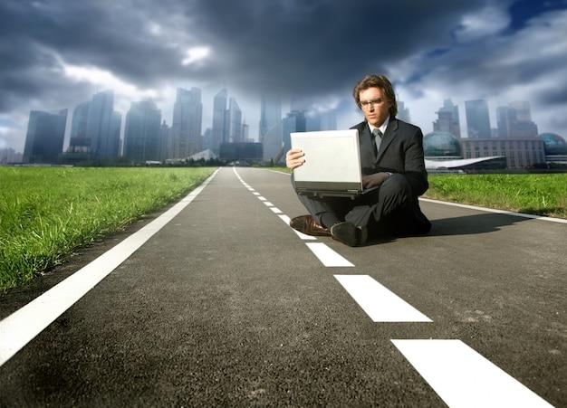 Biznesmen sadzający na ulicie pracuje na laptopie z miastem