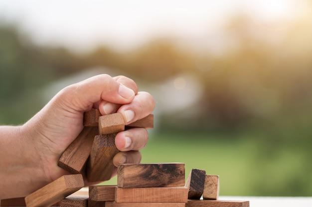 Biznesmen ściska drewnianego domino kwadratowych bloków wierza