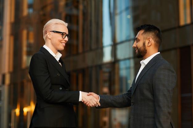 Biznesmen, ściskając rękę do interesu, on spotyka ją i pozdrawia ją na zewnątrz