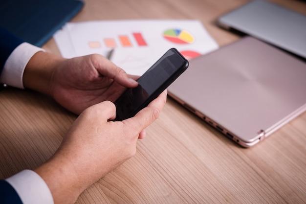 Biznesmen serching dane z smartphone między spotkaniem korporacyjnego sukcesu burzy mózgów