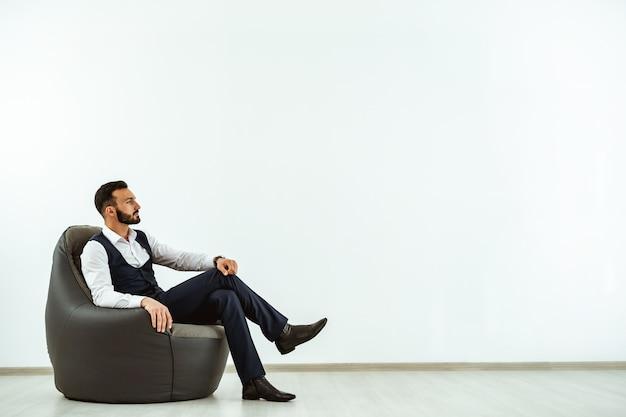 Biznesmen siedzący na krześle z torbą na tle białej ściany