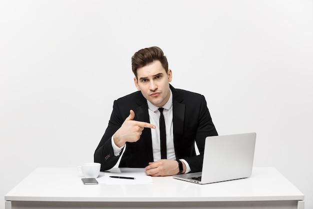 Biznesmen siedzący przy biurku wskazujący palcem na odizolowanym ekranie laptopa przystojny młody biznesmen wygląda...