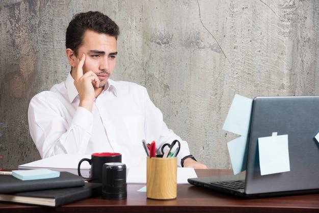 Biznesmen siedzi i myśli o pracy przy biurku.