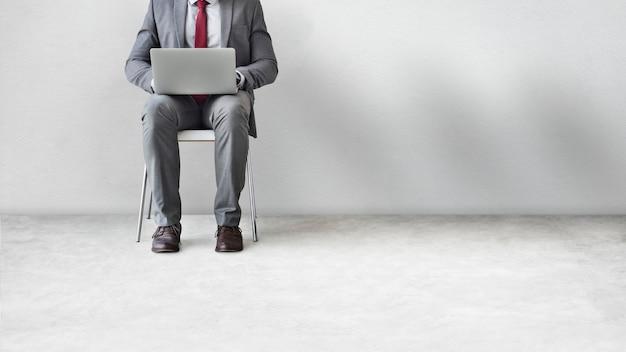 Biznesmen siedzi i pracuje na swoim laptopie