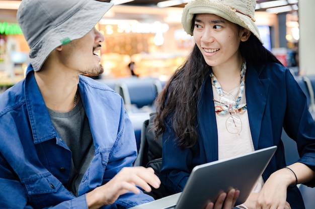 Biznesmen siedzi i używa laptopa do pracy na lotnisku, młoda osoba udaje się w podróż i posiada technologię komunikacji internetowej do pracy, gdy czeka w pomieszczeniu na odlot z lotniska