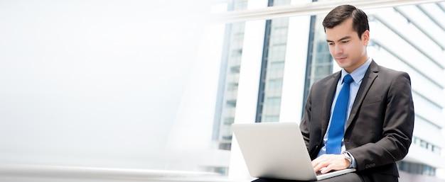 Biznesmen siedzi laptop i używa outdoors w mieście