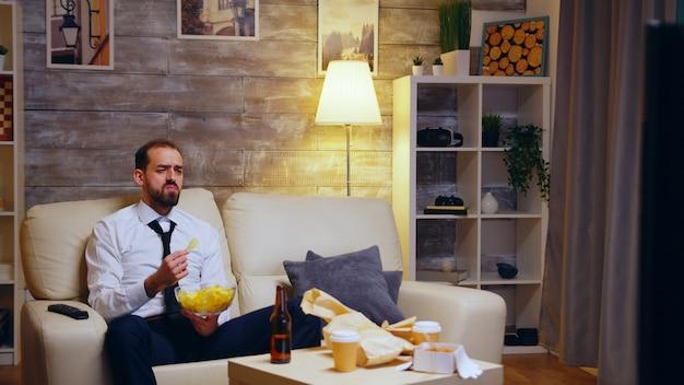 Biznesmen siedzi na kanapie jedzenie chipsów jedzenie telewizji. powiększ ujęcie.