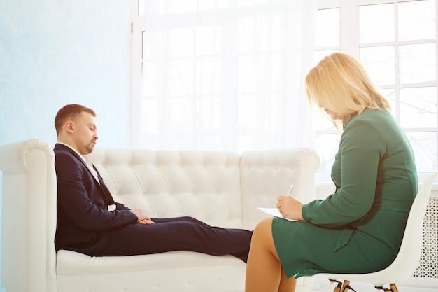 Biznesmen siedzi na kanapie rozmawiając z kobietą psychologiem, światło słoneczne
