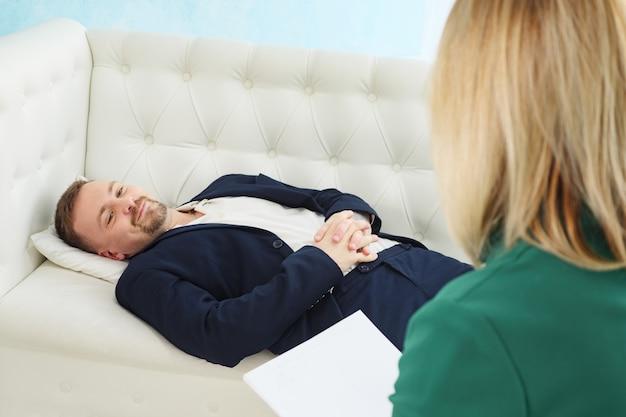 Biznesmen siedzi na kanapie, rozmawiając ze swoim terapeutą podczas sesji terapeutycznej.