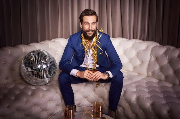 Biznesmen siedzi na kanapie w klubie nocnym