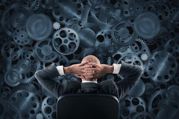 Biznesmen siedzi na krześle oglądając i analizując ścianę mechanizmów przekładni