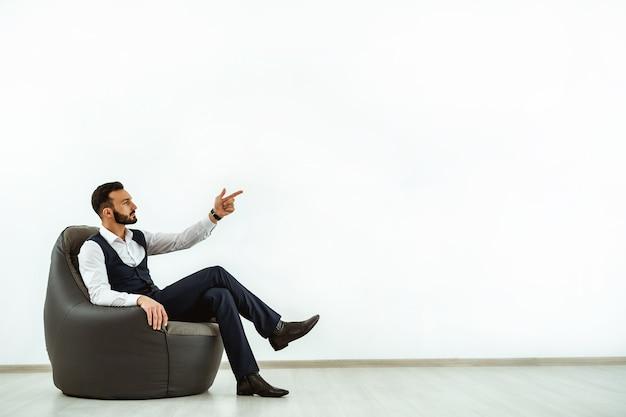 Biznesmen siedzi na krześle z torbą na tle białej ściany i gestykuluje