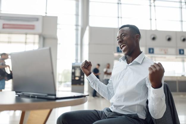 Biznesmen siedzi na laptopie w salonie samochodowym