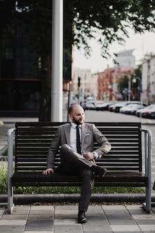 Biznesmen siedzi na ławce po pracy na ulicy miasta