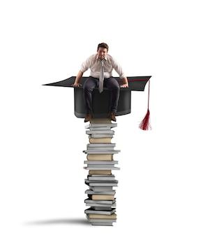 Biznesmen siedzi na stosie książek w kapeluszu ukończenia szkoły