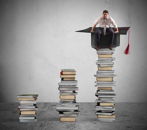 Biznesmen siedzi na stosie książek z kasztana