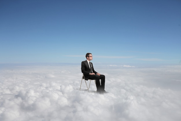 Biznesmen siedzi ponad chmurami