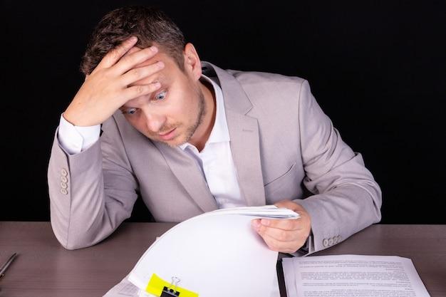 Biznesmen siedzi przy stole. na stole stosy teczek z dokumentami.