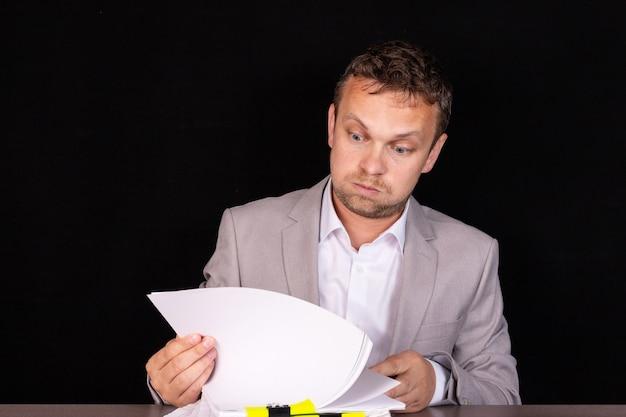 Biznesmen siedzi przy stole z dokumentami.