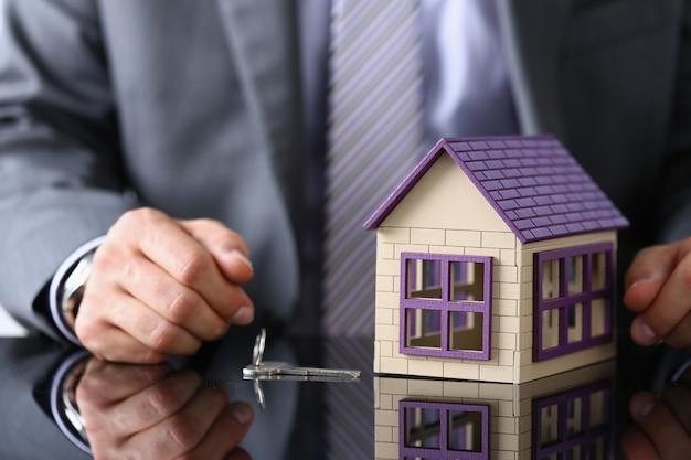 Biznesmen siedzi przy stole z zabawkami drewniany dom i metalowe klucze zbliżenie