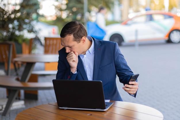 Biznesmen siedzi przy stoliku w kawiarni na ulicy, kaszle w dłoń, podczas przerwy w finansowej dzielnicy prowadzi rozmowę wideo przez telefon komórkowy. choroba podczas pracy.