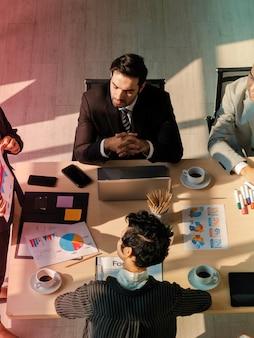 Biznesmen siedzi, śpi podczas słuchania spotkania konferencyjnego w biurze, przesadza, zmęczony pracą, leniwy w miejscu pracy
