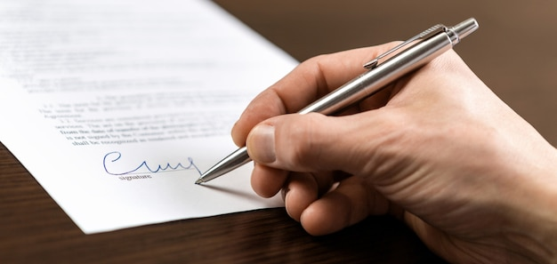 Biznesmen siedzi w biurze biurko i podpisuje umowę długopisem
