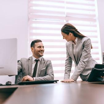 Biznesmen siedzi w biurze i mówi do swojej koleżanki. koncepcja firmy. razem wszyscy osiągają więcej.