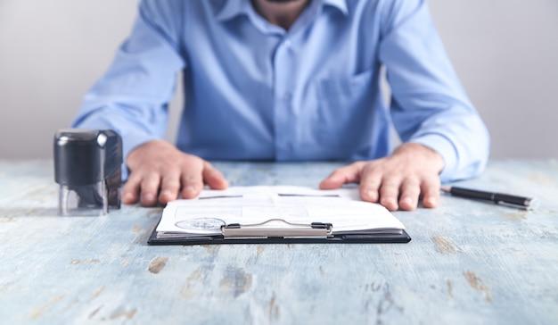 Biznesmen siedzi w biurze. pieczątka, dokument i długopis na biurku.