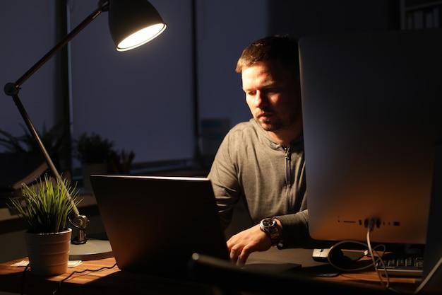 Biznesmen siedzi w biurze wieczorem przy stole