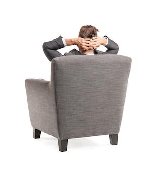 Biznesmen siedzi w fotelu na białym tle, widok z tyłu