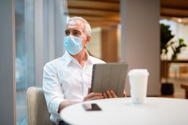 Biznesmen siedzi w kawiarni i korzysta z cyfrowego tabletu, nosząc maskę na twarz i poziome ujęcie z dystansu społecznego