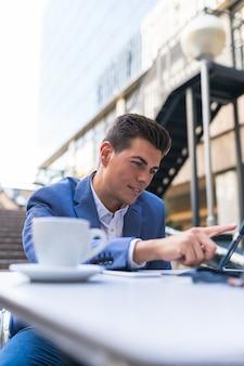 Biznesmen siedzi w kawiarni za pomocą laptopa. młody człowiek za pomocą laptopa na zewnątrz. pomysł na biznes.