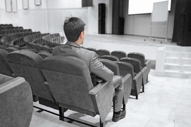 Biznesmen siedzi w pustej sali konferencyjnej. biznes i edukacja