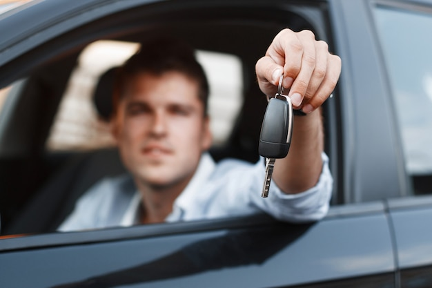 Biznesmen siedzi w samochodzie i daje kluczyk do samochodu