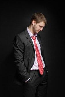 Biznesmen siedzi w wolnej pozycji, pochyla głowę.