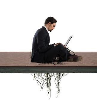 Biznesmen siedzi ze swoim laptopem z korzeniami pod