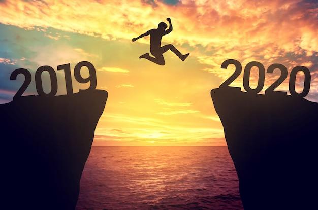 Biznesmen skacze między 2019 a 2020 rokiem.