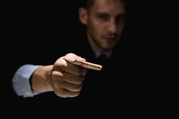 Biznesmen skrycie rozdaje pieniądze w ciemności