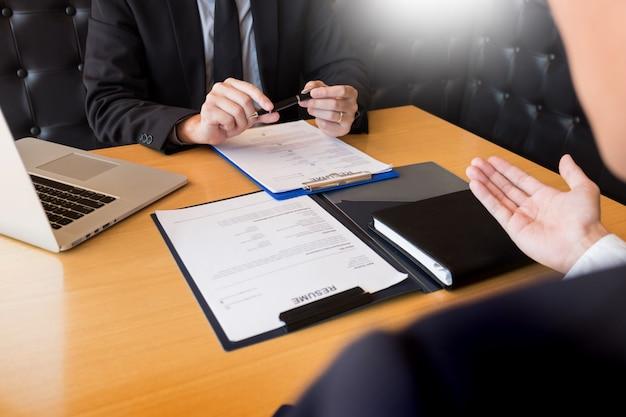 Biznesmen słucha młody atrakcyjny mężczyzna wyjaśnia o jego profilowym kandydata wywiada odpowiedzi