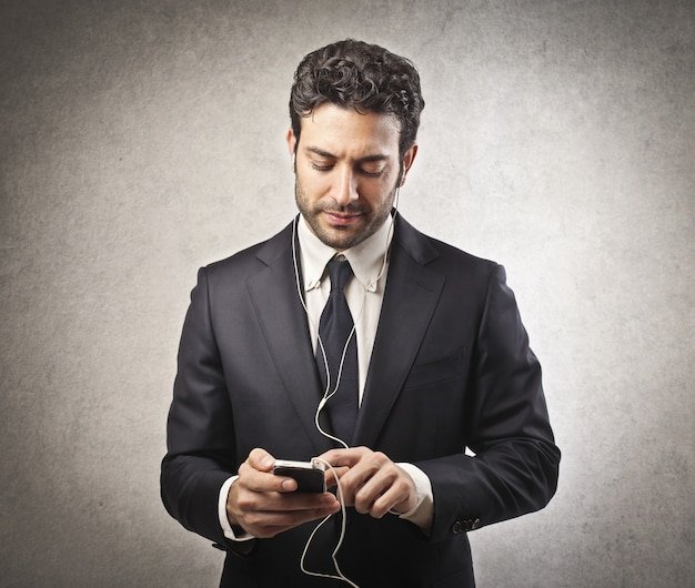 Biznesmen słucha muzyka na smartphone