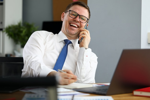 Biznesmen śmiejąc się rozmawia telefon z partnerem