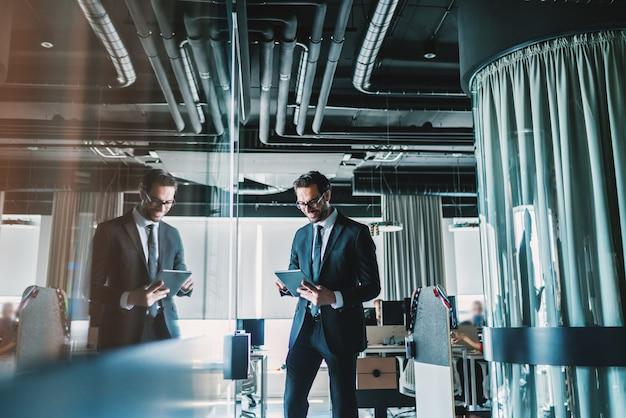 Biznesmen spaceru po firmie i za pomocą tabletu.
