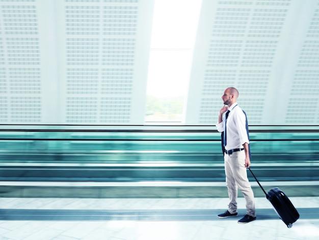 Biznesmen spacerujący z wózkiem na lotnisku