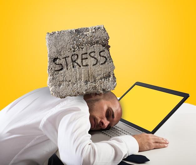 Biznesmen śpi na komputerze. koncepcja stresu i przepracowania. żółte tło