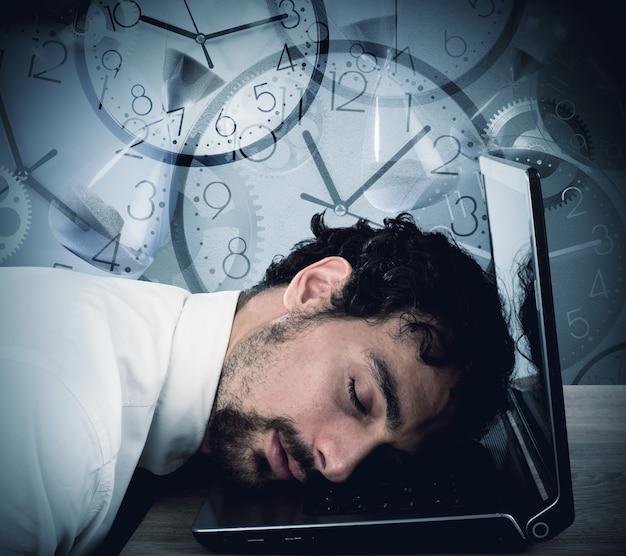 Biznesmen śpi na laptopie i ścianie z zegarkami
