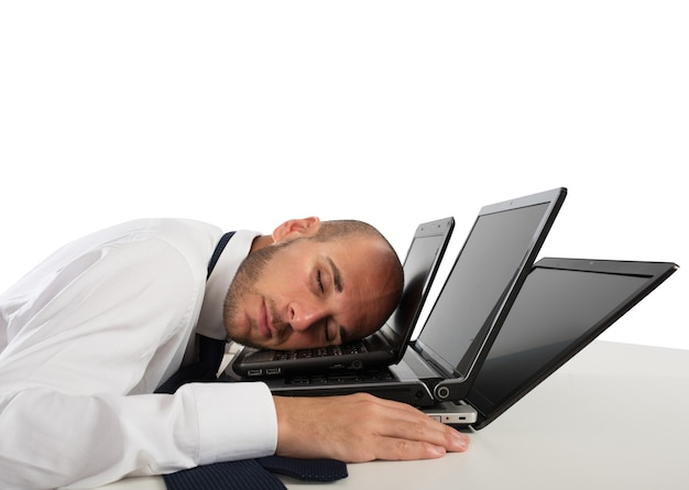 Biznesmen śpi przy komputerach na biurku