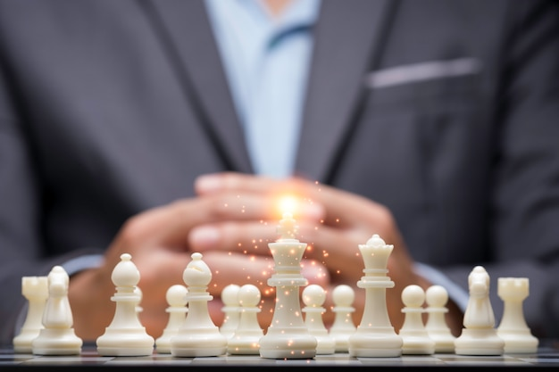Biznesmen splótł ręce za tłumem szachowych postaci za myślącą strategię planowania. biznesplan i strategiczna taktyka biznesowa z konkurencją.